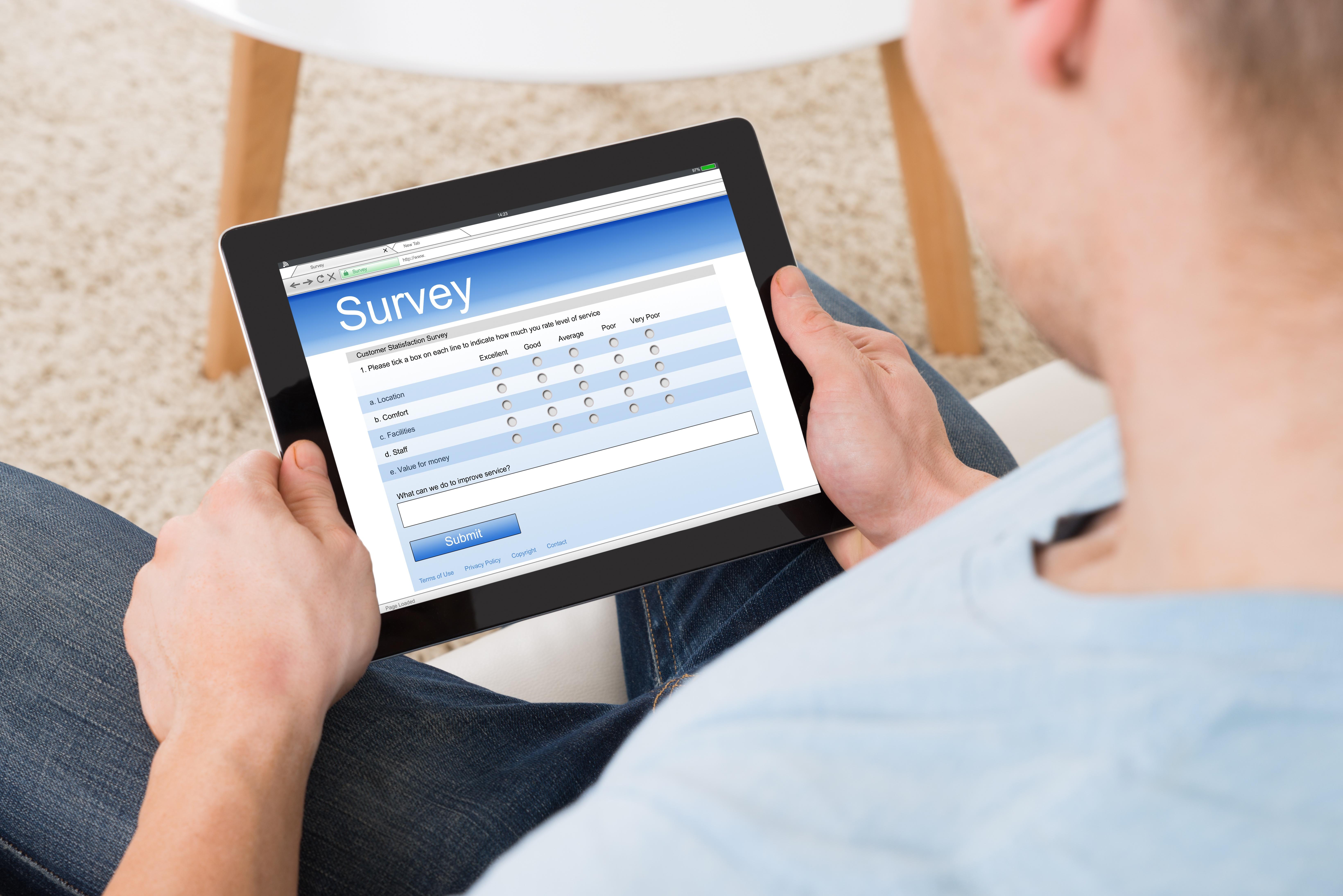 Man on iPad taking a CSAT survey