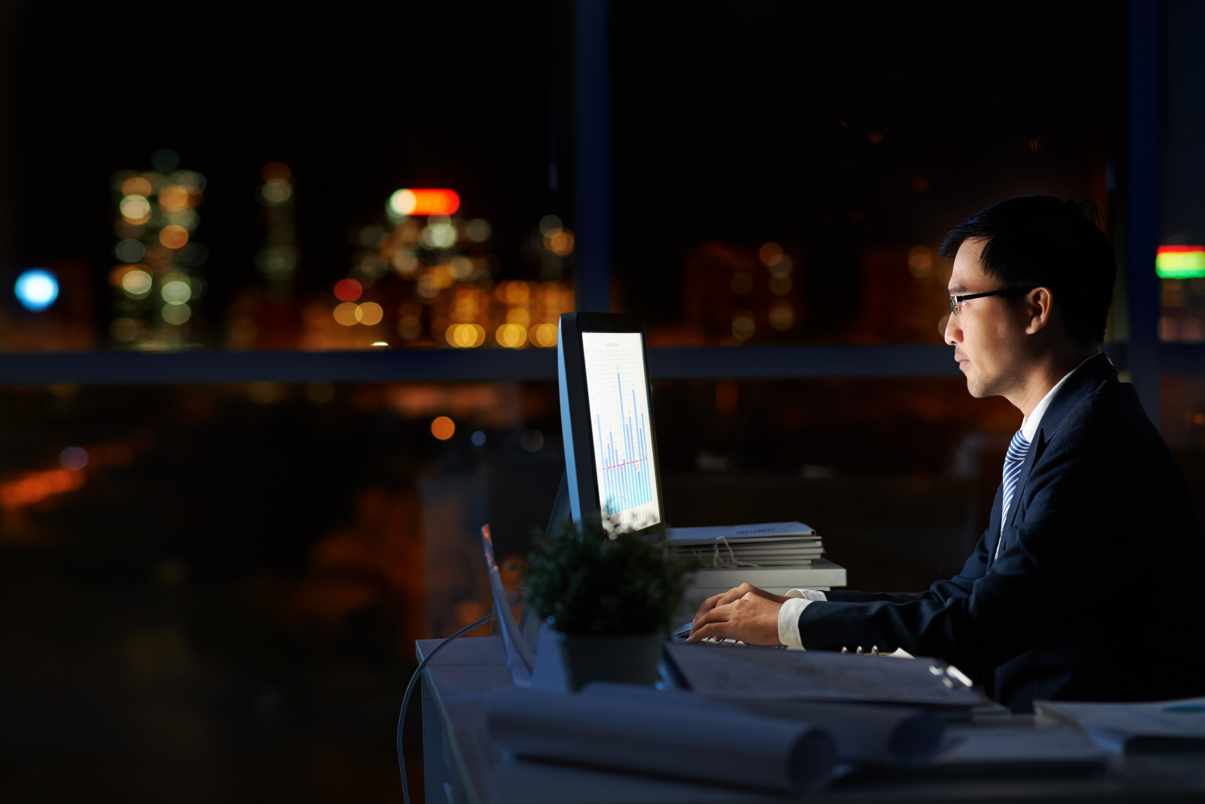 Man on computer trying to figure out how to reduce overtime