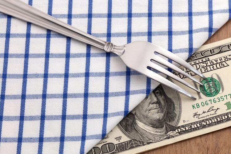 Money under tablecloth to represent how you can use checklists to cut restaurant labor costs